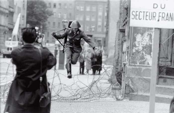 """An East German border guard jumping to West Berlin — the """"Leap of Freedom"""" — with only the clothes on his back."""