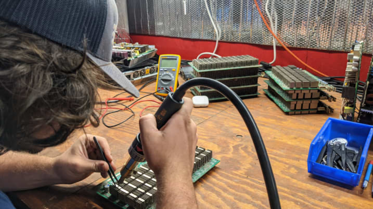 Nick Sears repairs hardware at the SCATE Ventures Inc. mining farm in Dallesport, Washington. Source