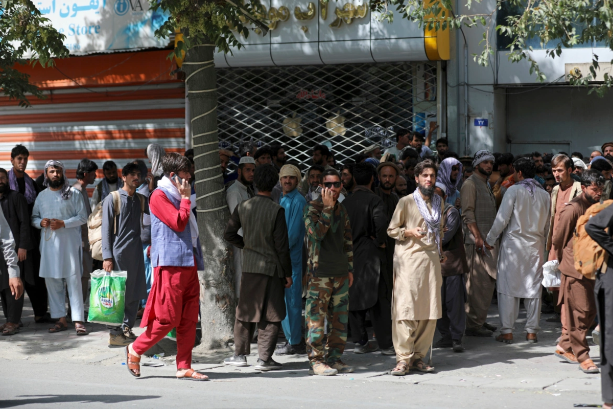 Afghans wait in long lines for hours to withdraw money in front of a bank in Kabul. [Rahmat Gul/AP Photo]